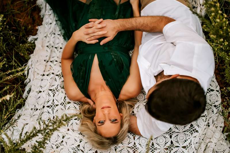Atlanta Couples Photographer, woman lays on blanket staring upward as her partner admires her