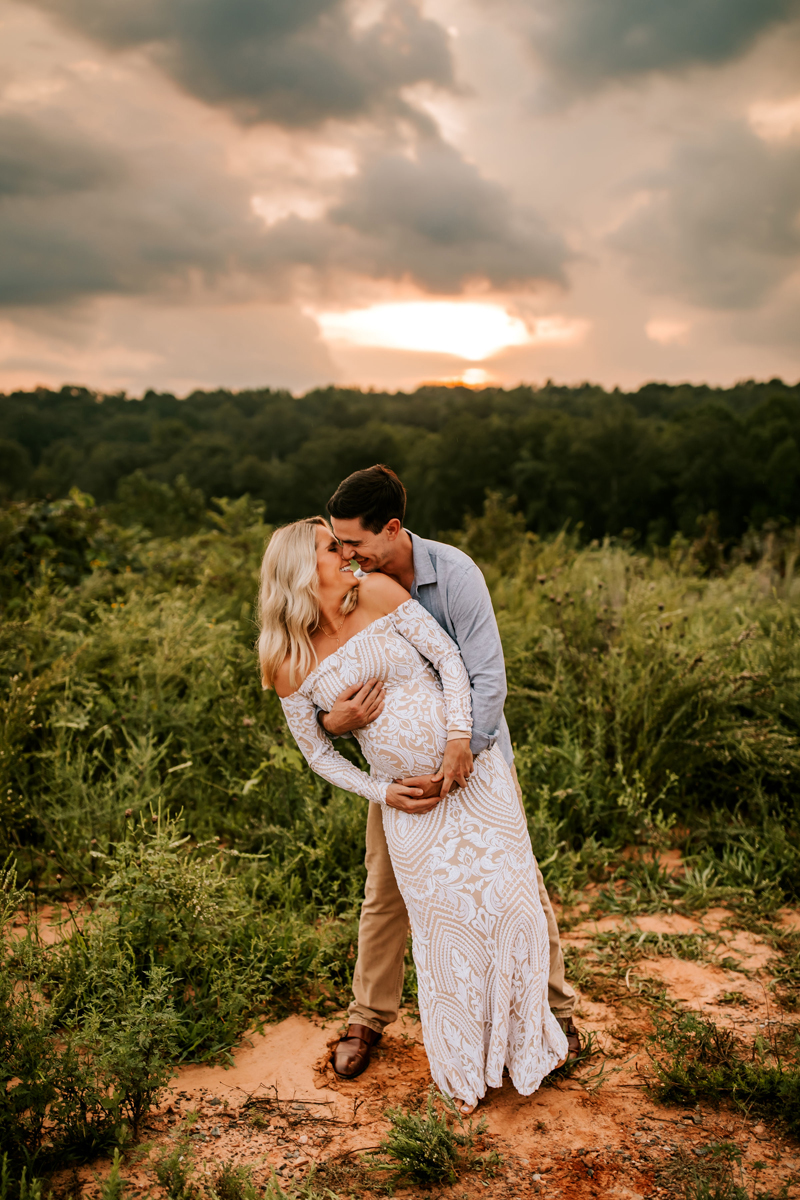 Atlanta Maternity Photographer, near trees, husband dips expectant wife as he leans in for kiss