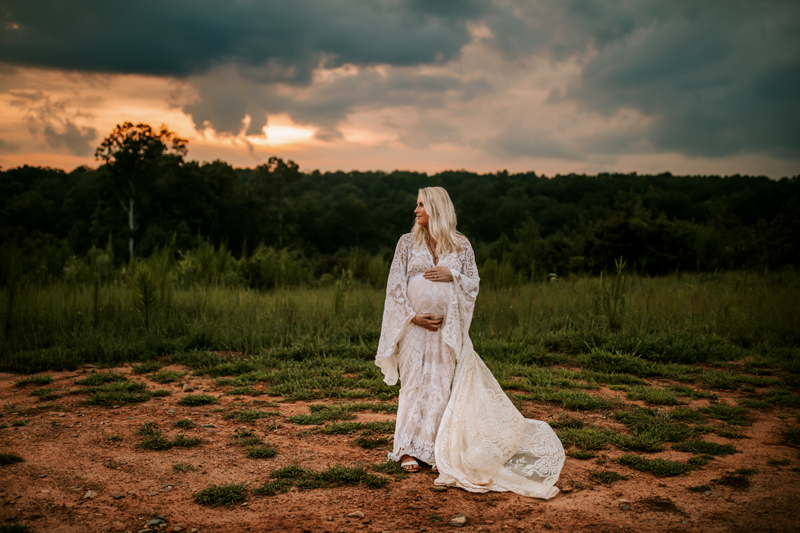 Atlanta Maternity Photographer, pregnant woman in white lace dress stands near forest at dusk