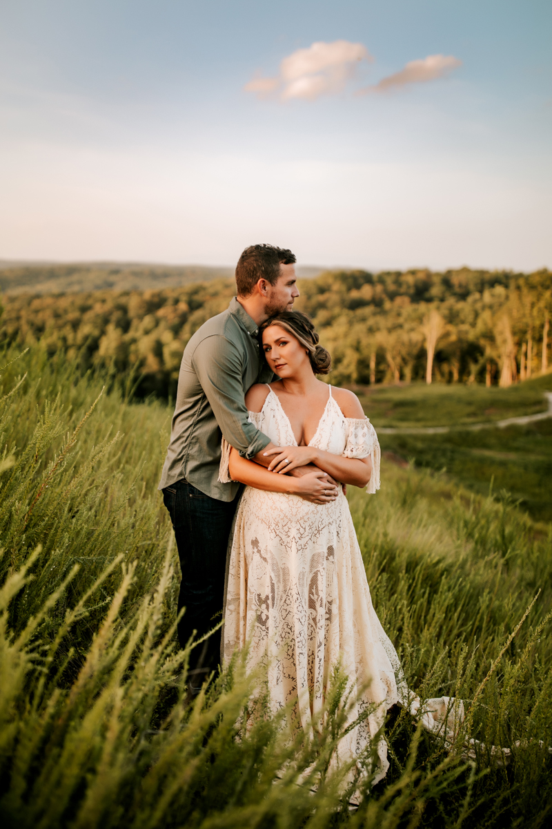 Atlanta Maternity Photographer, man holds pregnant woman in white dress thoughtfully on the hillside