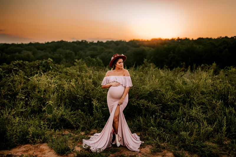 Atlanta Maternity Photographer, Pregnant woman wears dress, standing outdoors near trees and vegetation