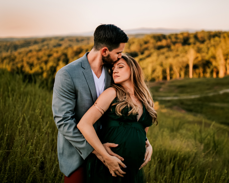 Atlanta Maternity Photographer, bearded man kisses expectant wife on forehead in grassy field