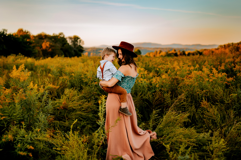 Atlanta Family Photographer, outdoors under a warm sunset mom holds and admires young son