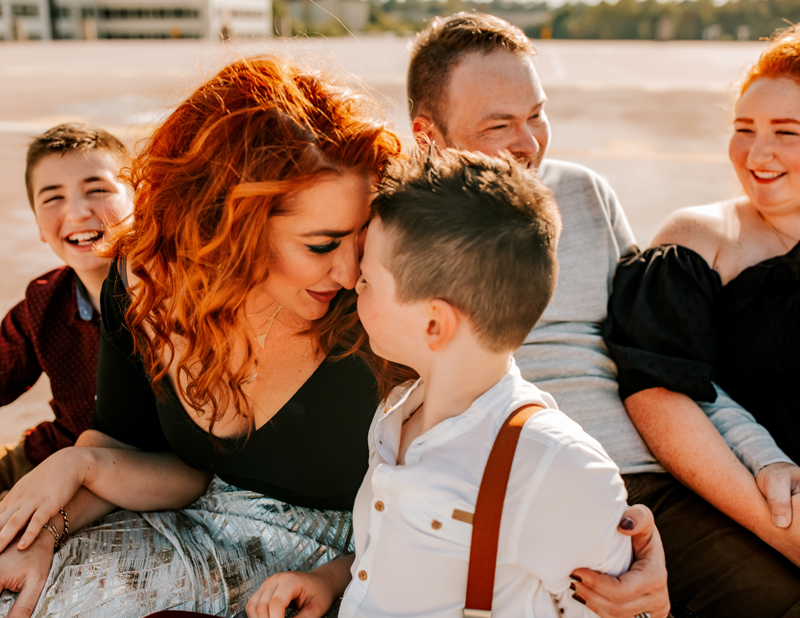 Atlanta Family Photographer, a family of five laughs together, mom embracing her young son
