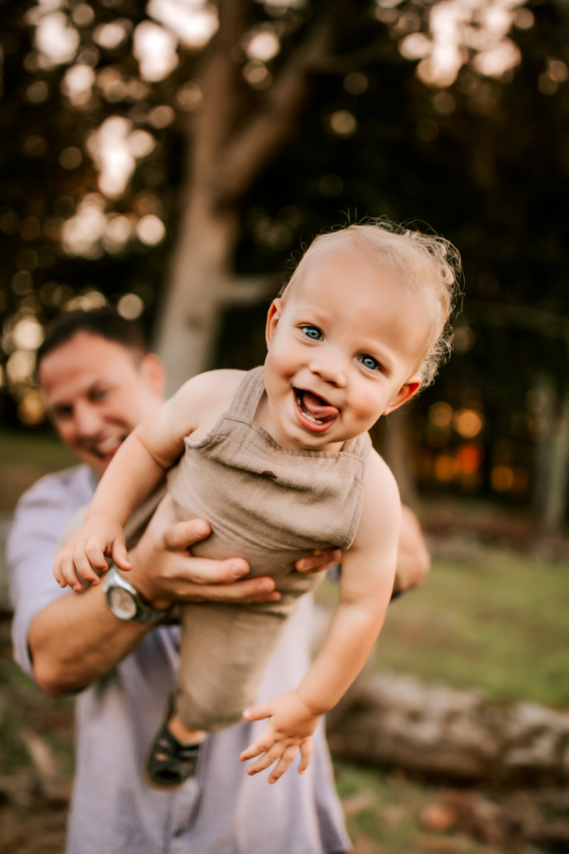 Atlanta Family Photographer, dad holds up smiling blue-eyed child in the air