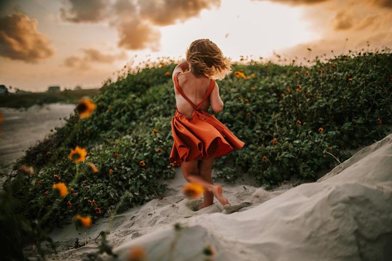 Atlanta Family Photographer, child runs through sand near beach and flower beds