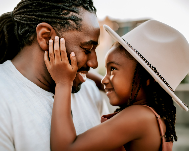 Atlanta Family Photographer, Dad holds daughter as she smiles and gazes directly into his eyes