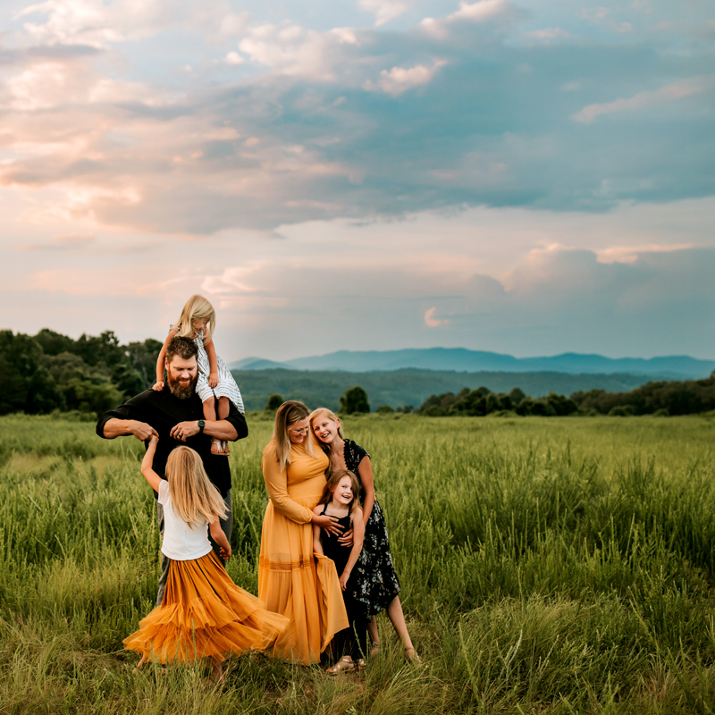 Atlanta Family Photographer, dad, mom, and four daughters smiling in a tall grassy field in the late aftrenoon