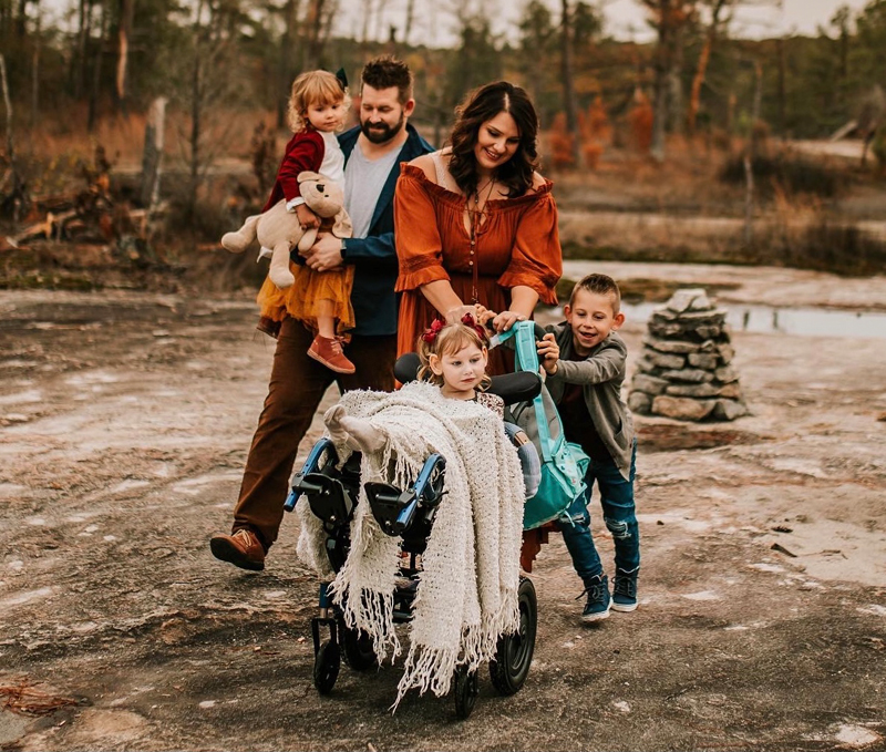Atlanta Family Photographer, family walks together outdoors as brother pushes sister in her wheelchair