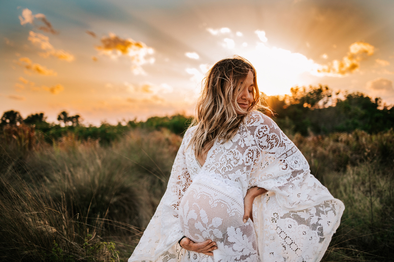 Atlanta Maternity Photographer, Expecting mom wears white lacy dress outside at sunset