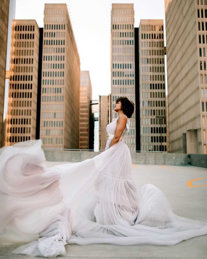 Atlanta Family Photographer, woman stands on a city rooftop as her flowing dress picks up in wind