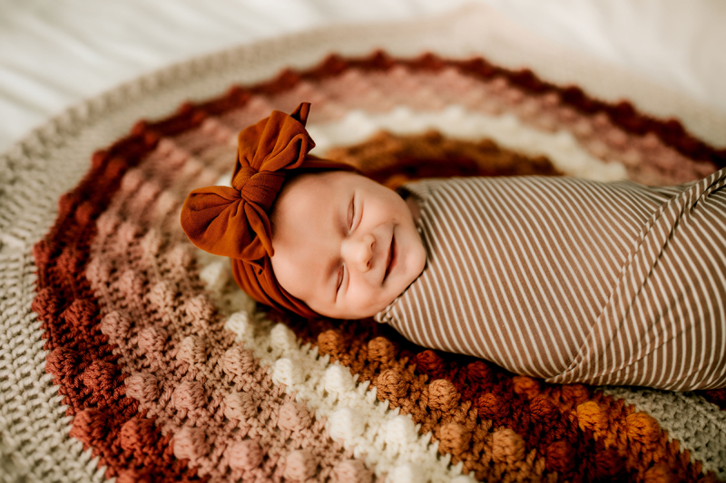 Atlanta Newborn Photographer, Baby wrapped in blanket with bow on head lays onknit rug