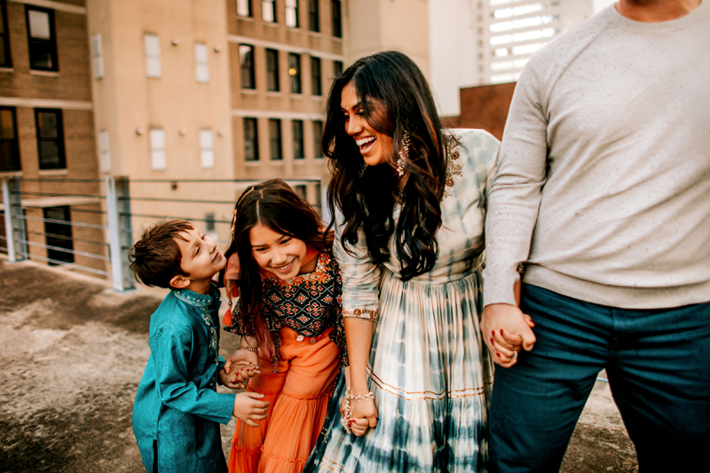 Atlanta Family Photographer, Man, woman daughter and son stand atop a city rooftop laughing