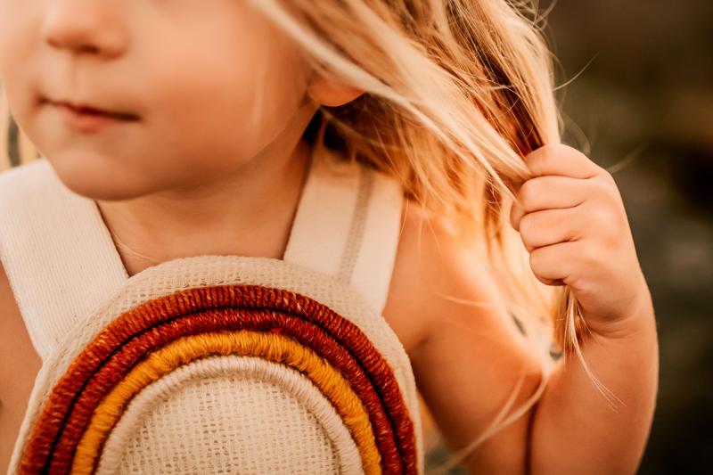 Atlanta Family Photographer, little girl holds onto her blonde hair as the sun shines on her