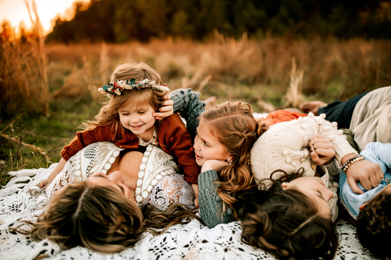 Atlanta Family Photographer, a woman and her 3 daughters lay on a crocheted blanket in a grassy field