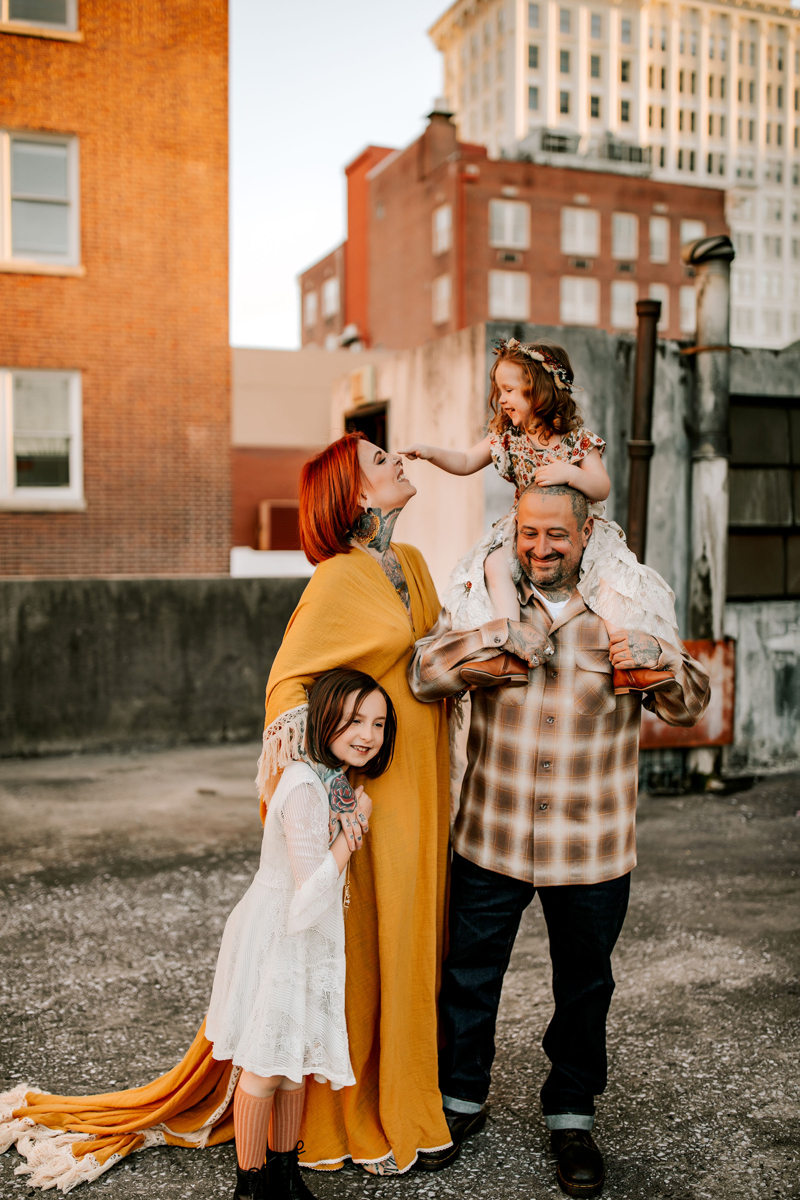 Atlanta Family Photographer, On a city rooftop a girl sitting on her dad's shoulders taps mom on the nose, another daughter hugs mom close
