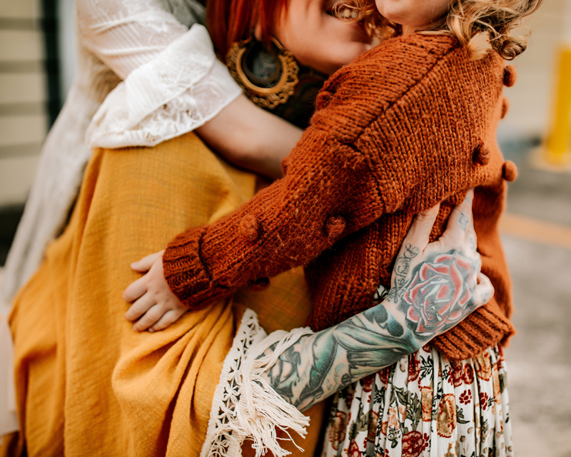 Atlanta Family Photographer, a mother embraces her young daughter, an older daughter embraces mom from behind