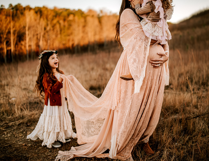 Atlanta Maternity Photographer, a mother holds her daughter, another daughter laughs as she holds up her mothers long dress train outdoors in the field