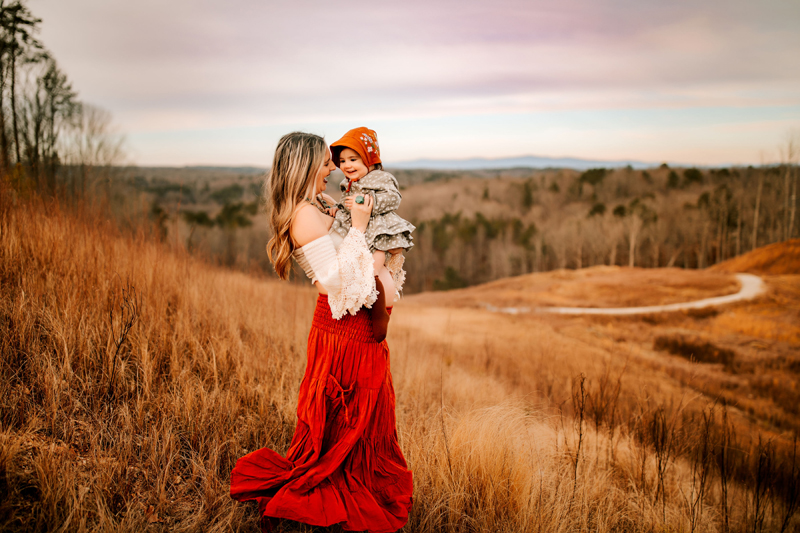 Atlanta Family Photographer, a woman holds her daughter, she stands on a dry grassy hillside at sunset