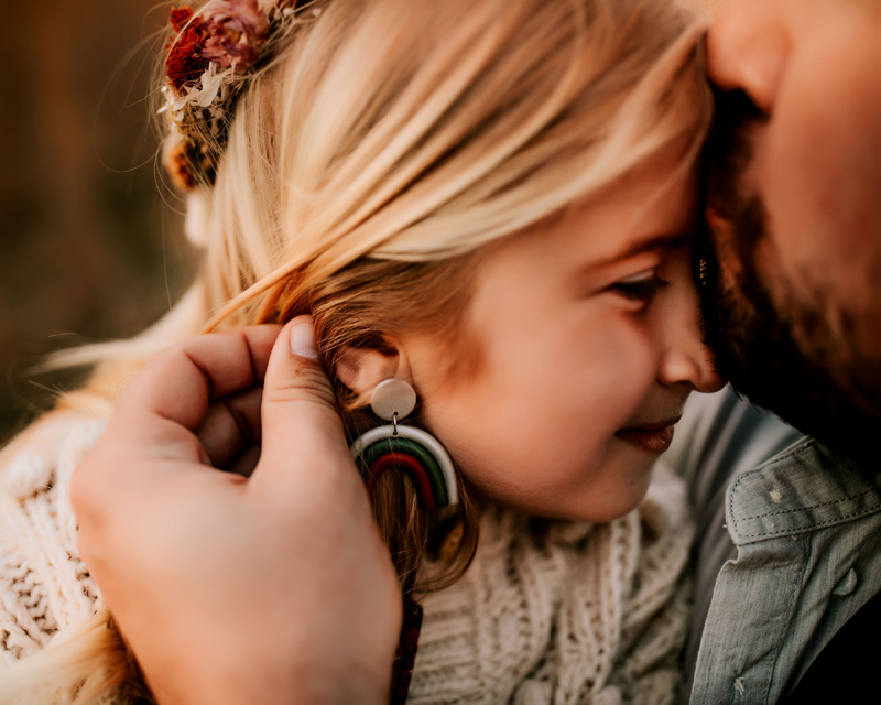 Atlanta Family Photographer, daughter gets a kiss from her bearded dad on the forehead, she smiles
