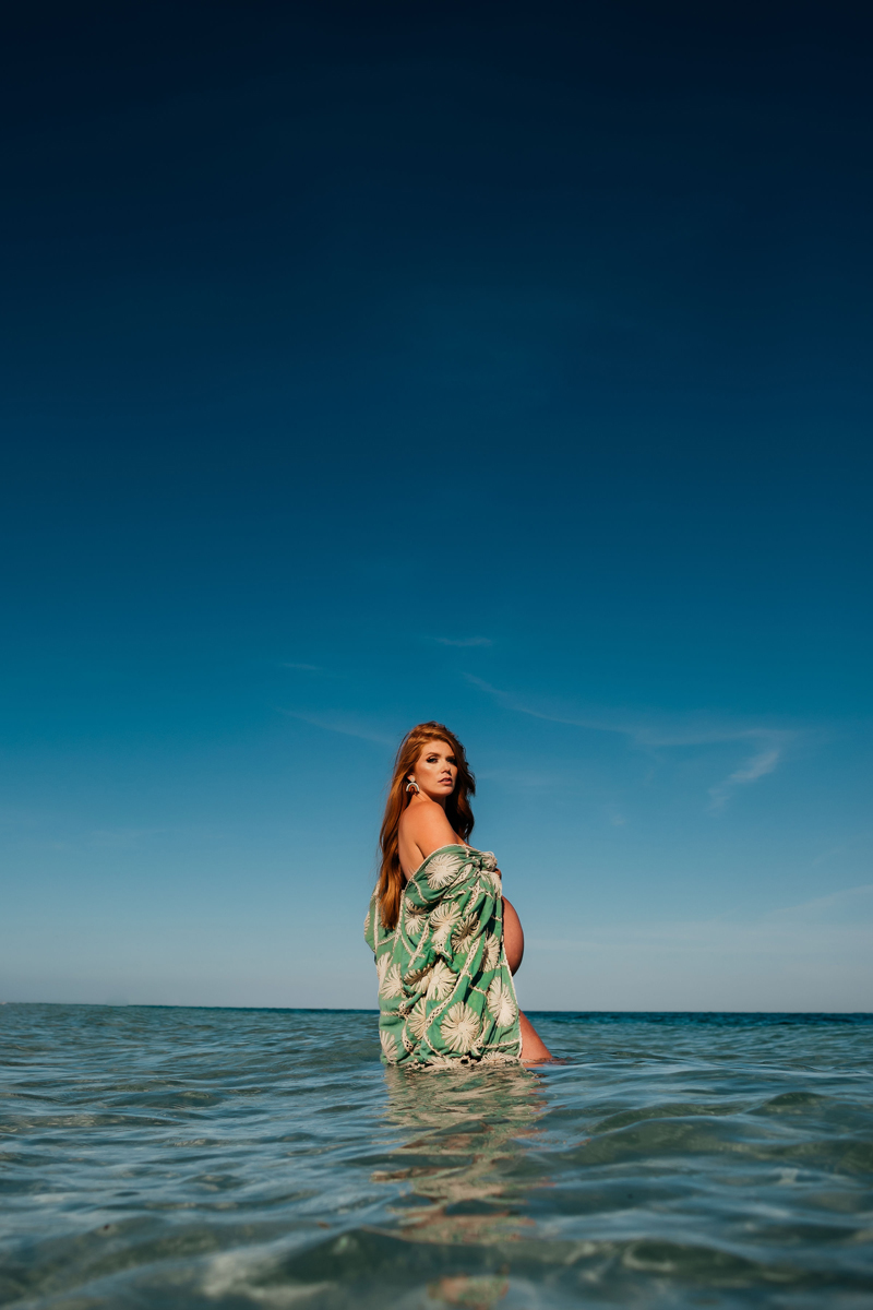 Atlanta Maternity Photographer, a pregnant woman lowers her kimono as she stands knee deep in the ocean