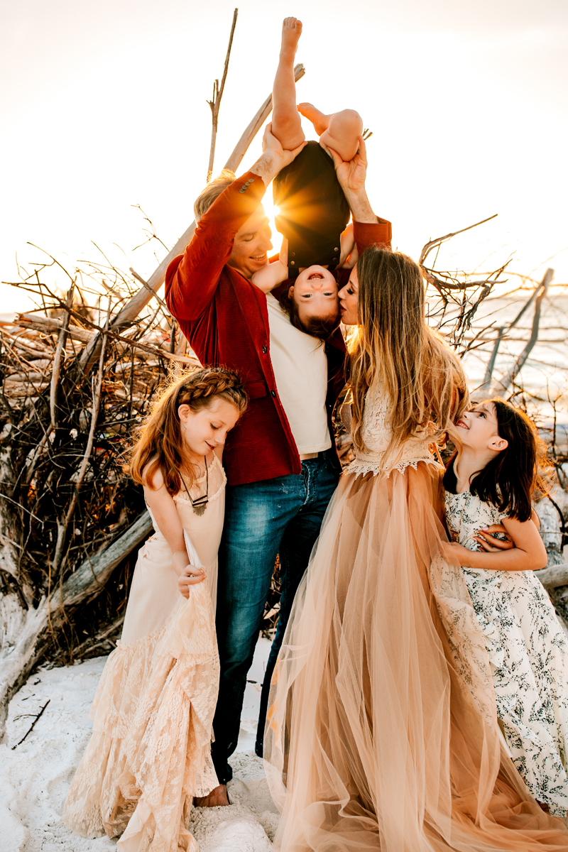 Atlanta Family Photographer, Dad holds young laughing child upside down and high in the air, mom kisses him, two other daughters smile beside them