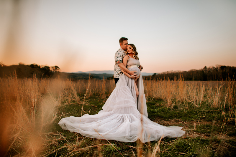Atlanta Maternity Photographer, a man holds onto his wife's pregnant belly, she wears a flowing white dress, they stand out in a field at sunset