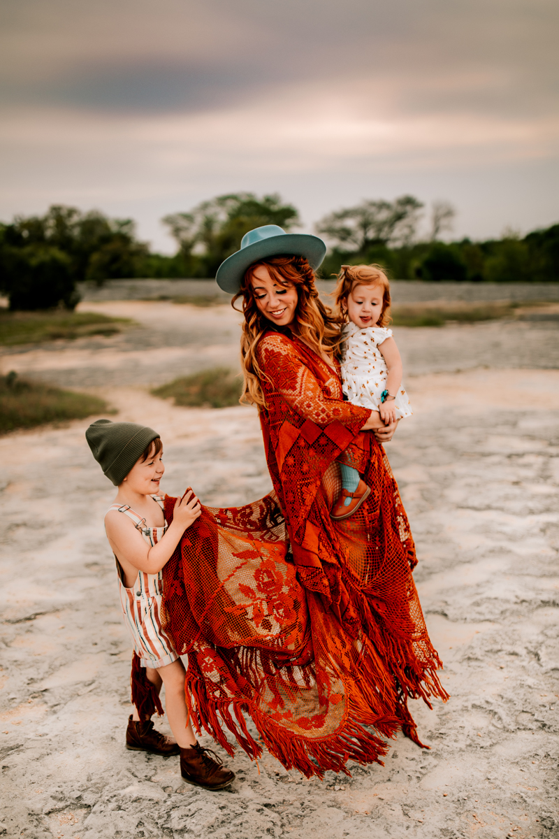 Atlanta Family Photographer, woman in red dress and turquoise hat walk in the sand with her two children