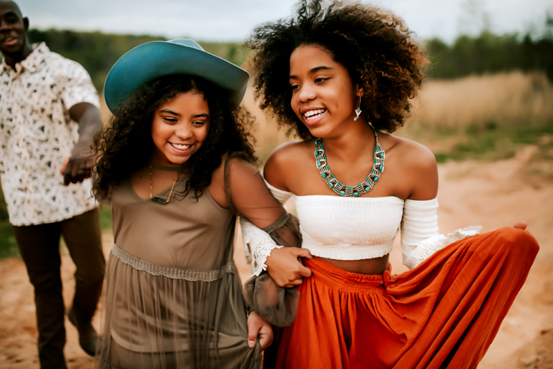 Atlanta Family Photographer, two girls walk and smile , their arms locked together, dad walks behind