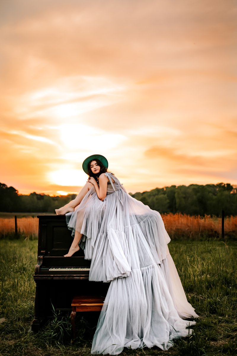 Atlanta Family Photographer, woman sits atop piano in a grassy field at sunset, she wears a beautifully long lavender dress that drapes over the piano