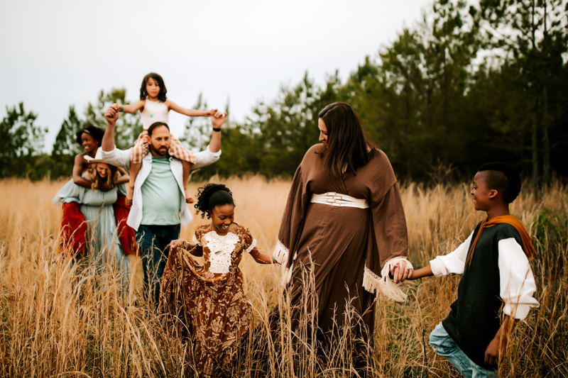 Atlanta Family Photographer, a family of seven walks together in a tall dry grassy field. They smile, laugh, and hold hands