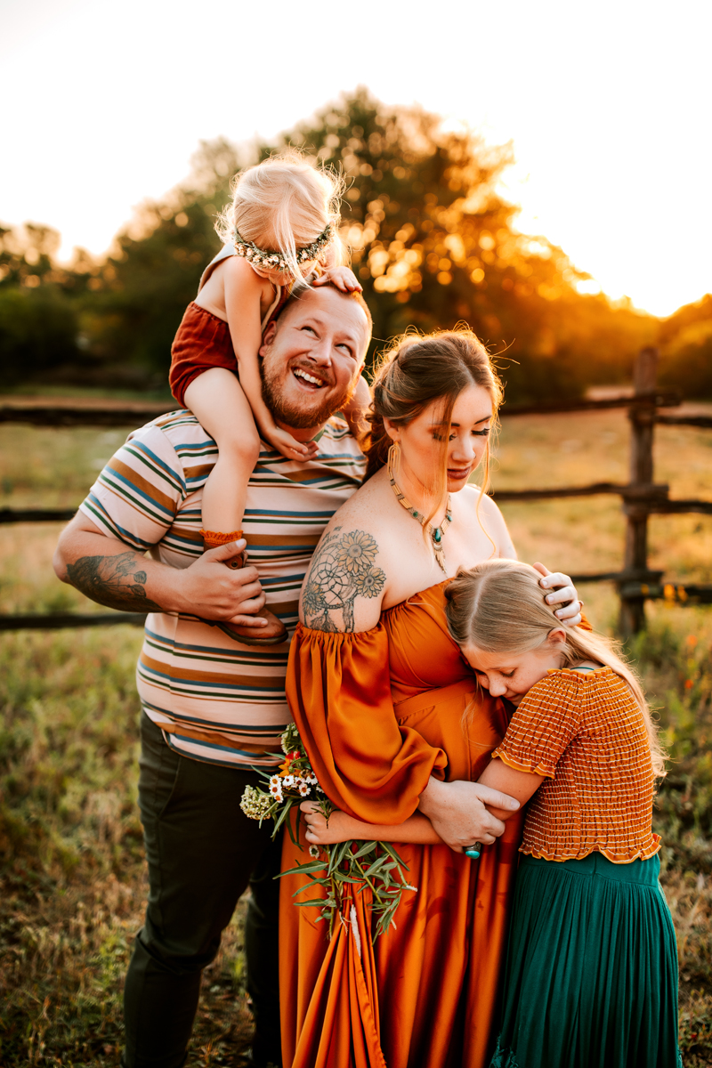 Atlanta Maternity Photographer, a family of four stand outdoors at sunset, the two daughters embrace their parents