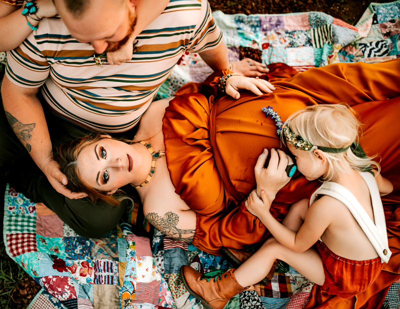 Atlanta Maternity Photographer, woman lays on her partners lap on a quilt as he gazes down at her, their children hug them