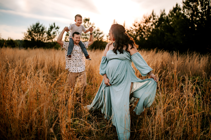 Atlanta Maternity Photographer, pregnant woman in dress walks in dry grassy field, man and son follow behind